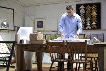 Uomo che avvolge l'immagine nell'involucro a bolle sul tavolo nel laboratorio di cornici — Foto stock