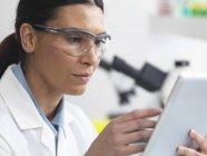 Scientifique visualisant les résultats des tests sur une tablette numérique en laboratoire — Photo de stock