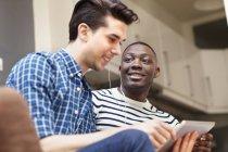 Due giovani uomini che ascoltano musica su tablet digitale sul divano del salotto — Foto stock