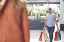 Mittlerer erwachsener Mann mit Einkaufstaschen hinter Frau hergelaufen — Stockfoto