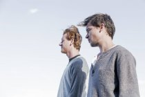 Low angle side view of young men looking away, Costa Smeralda, Sardinia, Italy — Stock Photo