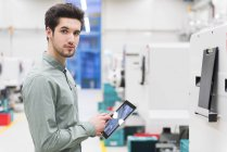 Portrait of male worker using digital tablet at tool manufacturing plant — Stock Photo