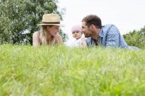 Mother and father with baby daughter on grass — Stock Photo