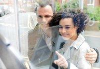 Пара вікно покупки, молода жінка, вказуючи на скло — стокове фото