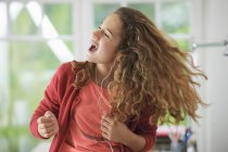Niña con auriculares, bailando a la música - foto de stock