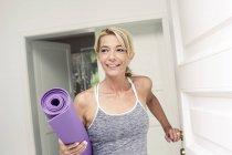 Mujer madura en puerta llevando la estera de la yoga - foto de stock