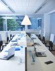 Порожній офісний інтер'єр з довгою стільницею з ноутбуками та лампою для освітлення — стокове фото