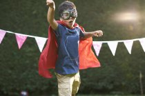 Boy wearing goggles and cape in superhero stance — Stockfoto