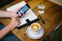 Куповані образ жінки за допомогою смартфона столом з кави — стокове фото