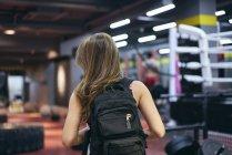 Rückansicht des jungen Frau mit Rucksack Vorbereitung für Fitness-Studio — Stockfoto