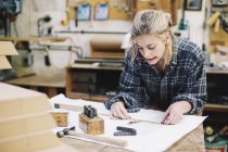 Young craftswoman measuring blueprint on workbench in pipe organ workshop — Stock Photo