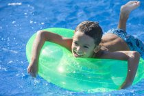 Boy lying on inflatable ring in garden swimming pool — Stock Photo