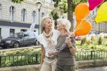 Mère et fille se promenant rue bouquet ensemble, tenant des ballons — Photo de stock