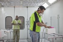 Man spraying box in carpenters workshop — Stock Photo