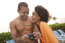 Couple laughing at photographs on digital camera at hotel poolside, Rio De Janeiro, Brazil — Stock Photo