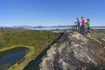 Велосипедисти дивляться на озеро кратера в Національний парк, Неджавелліr, Ісландія — стокове фото