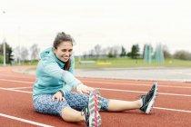 Jovem na pista de corrida, exercício, alongamento — Fotografia de Stock