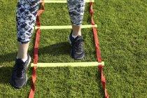 Ноги молода жінка заняття на спритність сходи — стокове фото