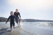 Père et fils courir sur la plage, Loch Eishort, Isle of Skye, Hébrides en Écosse — Photo de stock