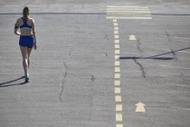 Rear view of young female runner running in parking lot — Stock Photo