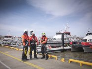 Offshore windfarm engineers on quayside with boats in the background — Stock Photo