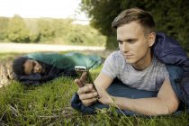 Молодой человек лежит спальный мешок смс на смартфоне в поле — стоковое фото