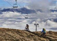 Deux vététistes sous les téléphériques, Valais, Suisse — Photo de stock