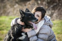 Портрет середины взрослой женщины, целуя ее собака в поле — стоковое фото