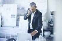 Деловой человек в чате на смартфоне при использовании офисного ноутбука — стоковое фото