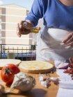 Abgeschnittenes Bild einer Frau, die am Küchentisch Olivenöl auf Brot gießt — Stockfoto