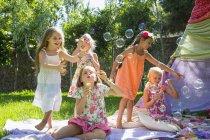 Ragazze che soffiano bolle in estate festa in giardino — Foto stock