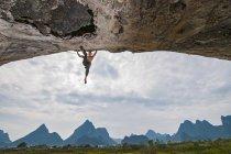Живописным малым углом зрения рок-альпинист, висит от Арка пряной лапши 5.14 c, Белая гора, Yangshuo, Гуанси-Чжуанском, Китай — стоковое фото