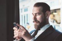 Бізнесмен читання смартфон оновлення в кафе — стокове фото