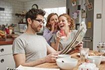Mittlere erwachsene Mann am Frühstückstisch lesen Zeitung, während Tochter und Mutter lachen — Stockfoto
