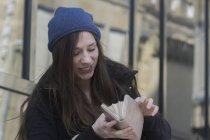 Frau blickt lächelnd auf offene Handtasche — Stockfoto