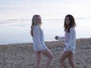 Deux jeunes femmes debout sur la plage au crépuscule — Photo de stock