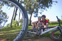 Велосипедисти на траві за допомогою смартфона — стокове фото