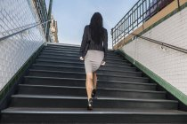 Businesswoman walking up stairs from metro station, Paris, France — Stock Photo