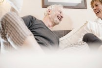 Couple laughing in bed, differential focus — Stock Photo