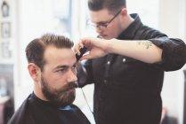 Friseur schneidet Kundenhaare mit Haarschneidemaschinen — Stockfoto
