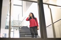 Young woman on staircase using cell phone — Stock Photo