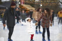 Дівчинка тримає батьки руки Лід катання на ковзанах, посміхаючись — стокове фото