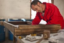 Carpenter working on wooden frame — Stock Photo