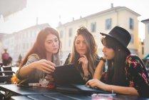 Три молодих жінок, які дивляться на цифровий планшет на тротуарі кафе — стокове фото