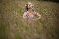 Зрелая женщина, медитирующая на траве — стоковое фото