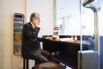 Homme d'affaires senior chat sur smartphone dans café hublot — Photo de stock