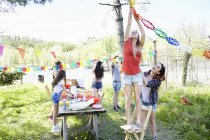 Young woman hanging up bunting over picnic table in garden — Stock Photo