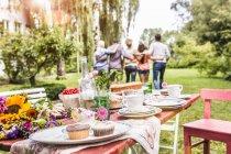 Gruppo di amici che si abbracciano, tavolo da festa in giardino con cibo in primo piano — Foto stock