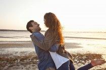 Paar amüsiert sich am sonnigen Strand — Stockfoto