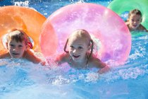 Three children swimming with inflatable rings in garden swimming pool — Stock Photo